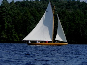 Idem class sailboat under sail on Upper St. Regis Lake.