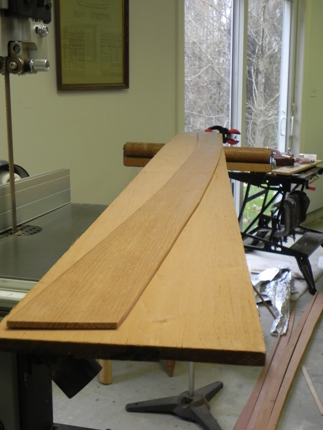 """A round 7 spiled plank lying on 8"""" wide planking stock."""