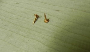Close up of annealed copper tacks showing triangular cross section of shaft.