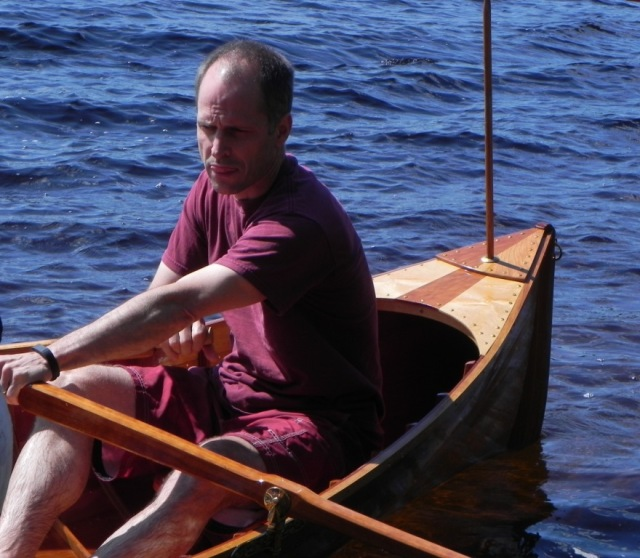 Son Stew at the helm of the Thankful using pinned oars.