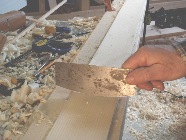 Scraper with shaped blade used in final smoothing of the backed out plank.