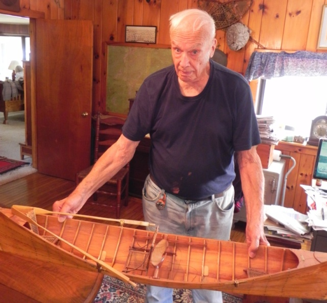 Tom Bissell holding his guideboat model.