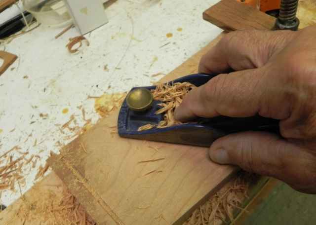 Finishing forming the curve in the seat back using a block plane with a curved sole.