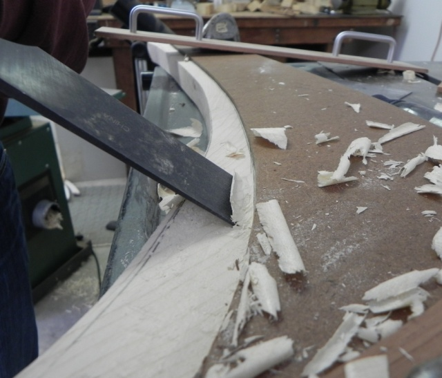 Using a chisel to cut away the excess to form the rabbet.