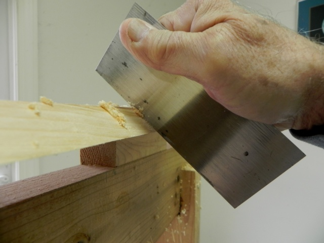 Using a cabinet scraper to finish off the bottom board bevel.